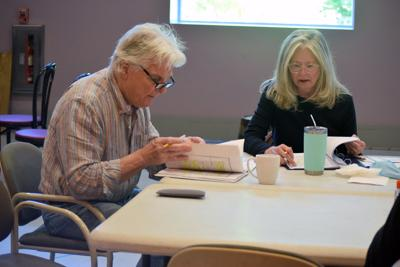 A man and a woman sit a table reading a script