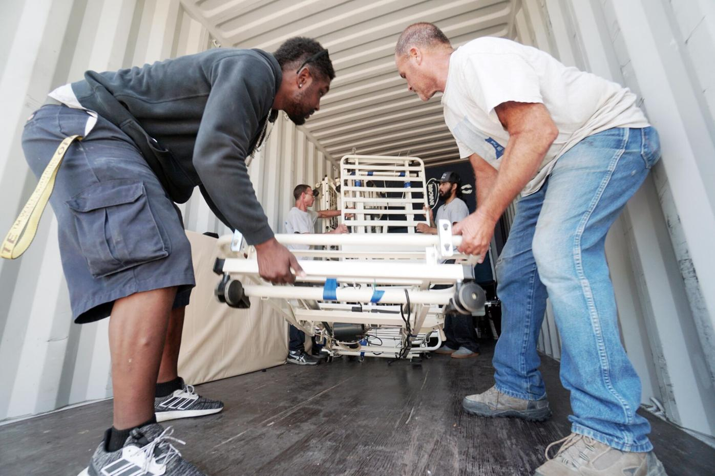 Movers pack beds into truck