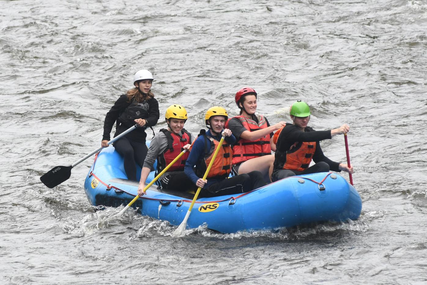 Five people navigate a raft down the river