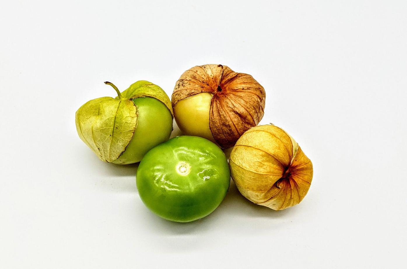 a green tomatillo and three tomatillos with husks