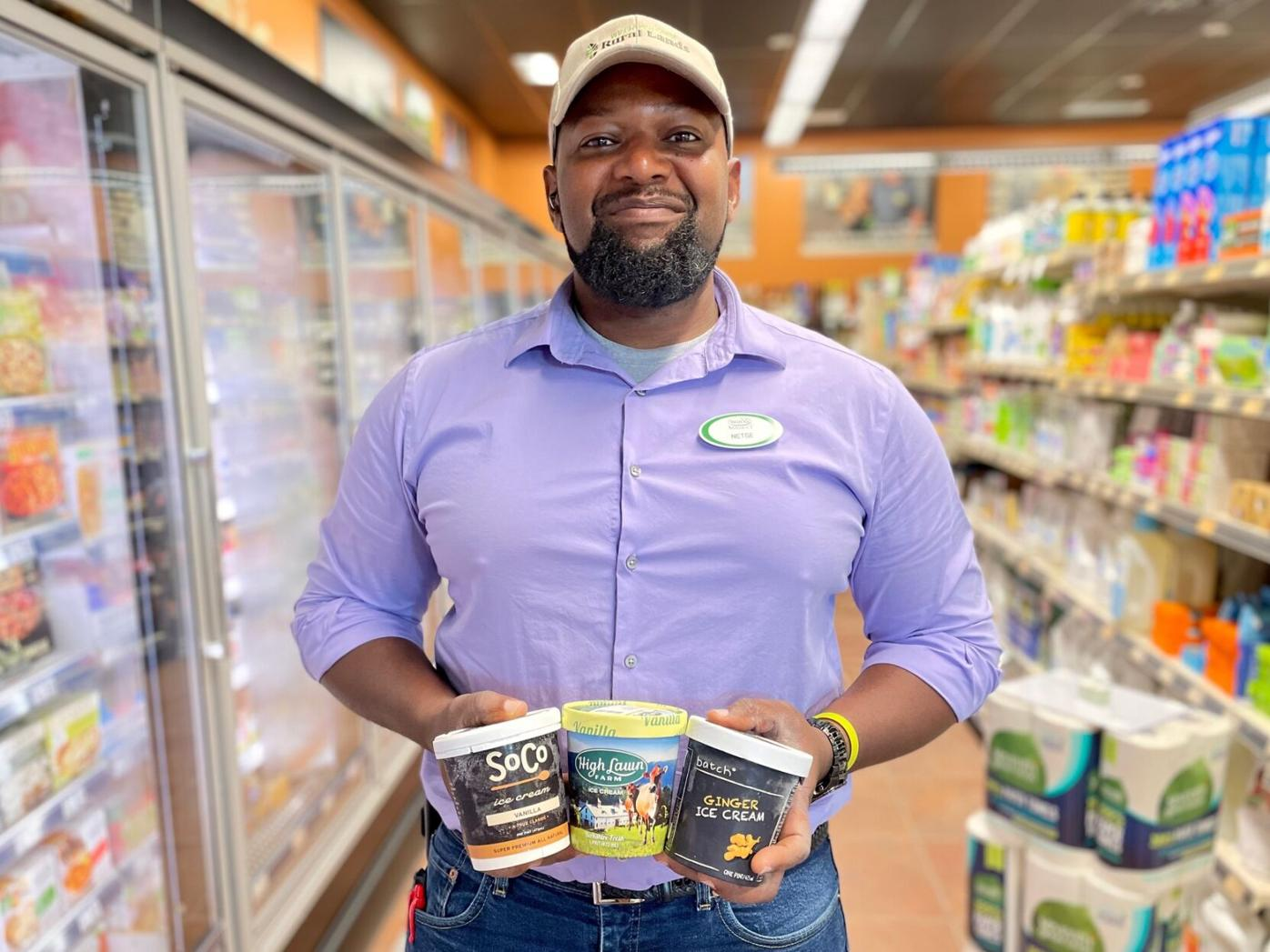 Co-op manager poses in the frozen aisle with three pints of ice cream
