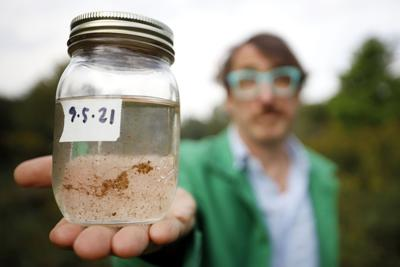 Reed Anderson holding jar of dirty tap water