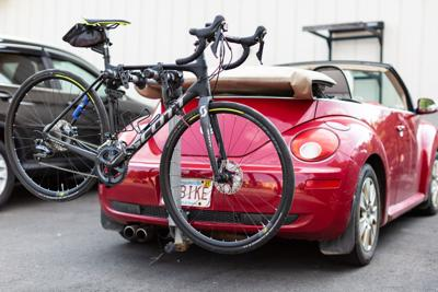 A road bike strapped to the rear of a red convertible
