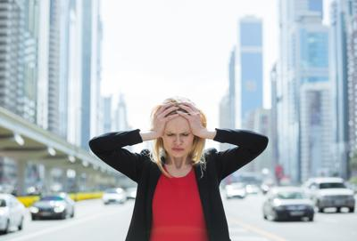 Stressed business woman in the busy city.