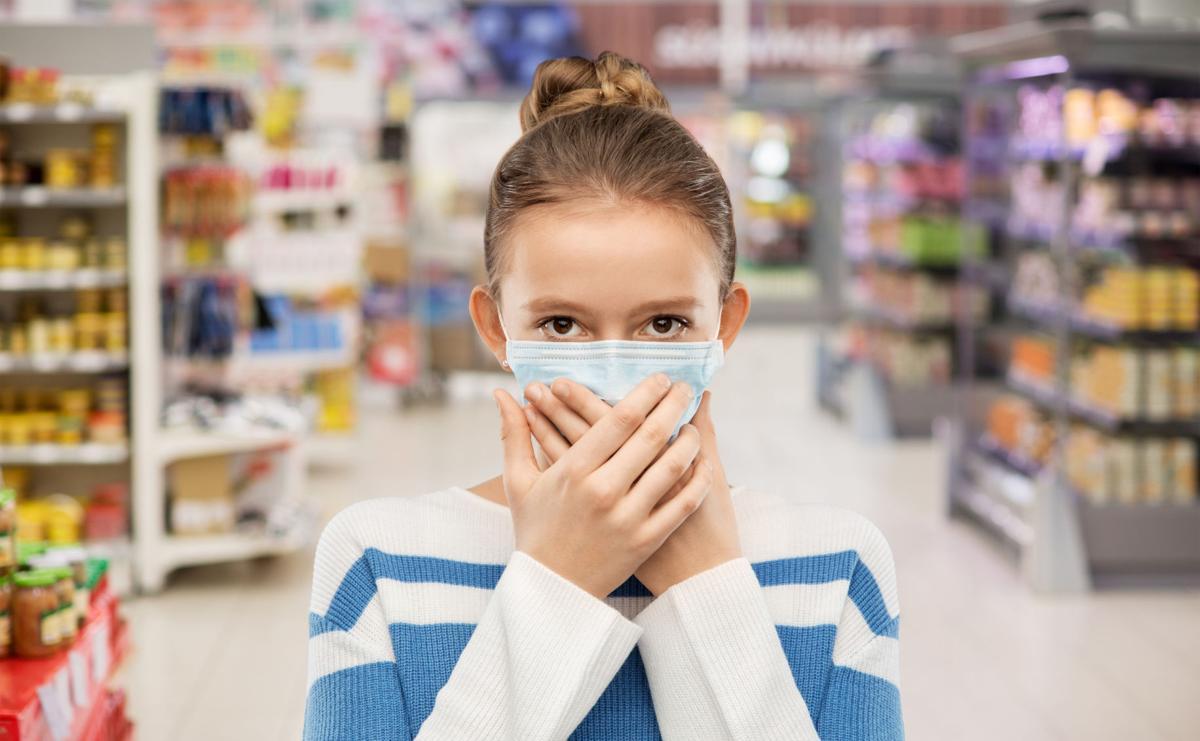 teenage girl in medical mask at supermarket