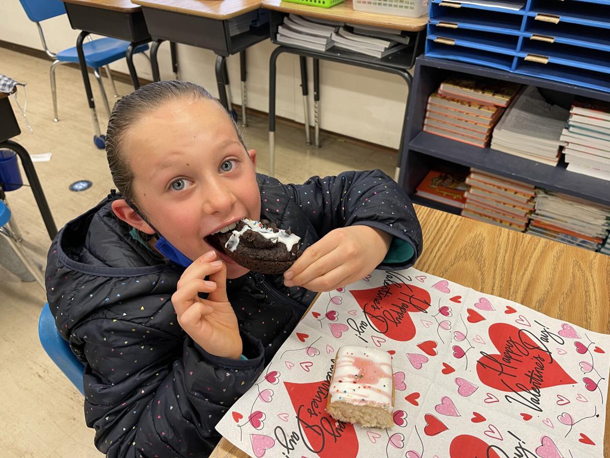Kaitlyn Charette enjoys her Raspberry Delight Donut