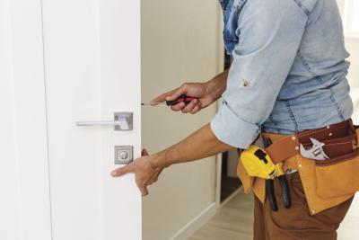 young repairman checking new door lock