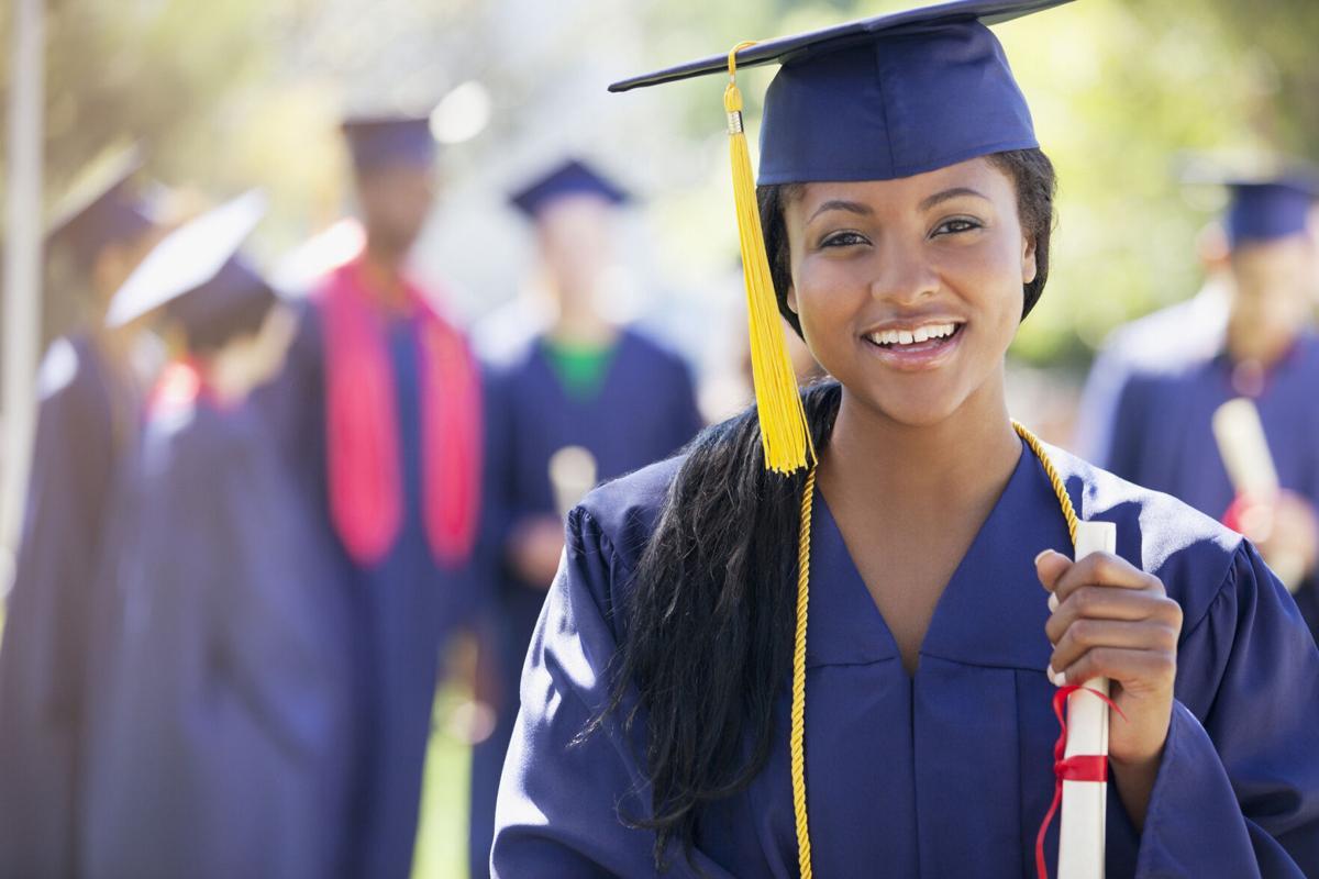 Smiling graduate holding diploma