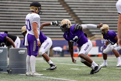 8cc4deafb14 The JMU defensive line unit works on footwork and quickness off the line  during training camp.