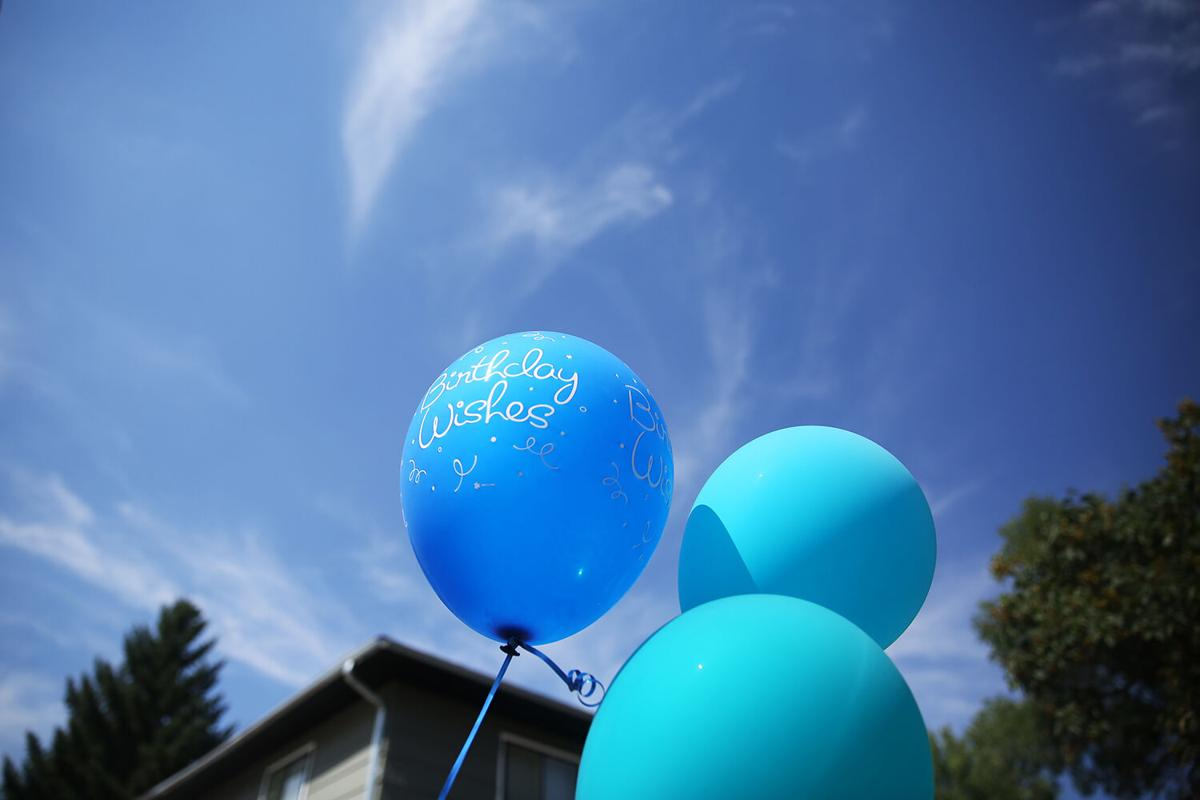 Blue and purple birthday balloons were hung along the fence