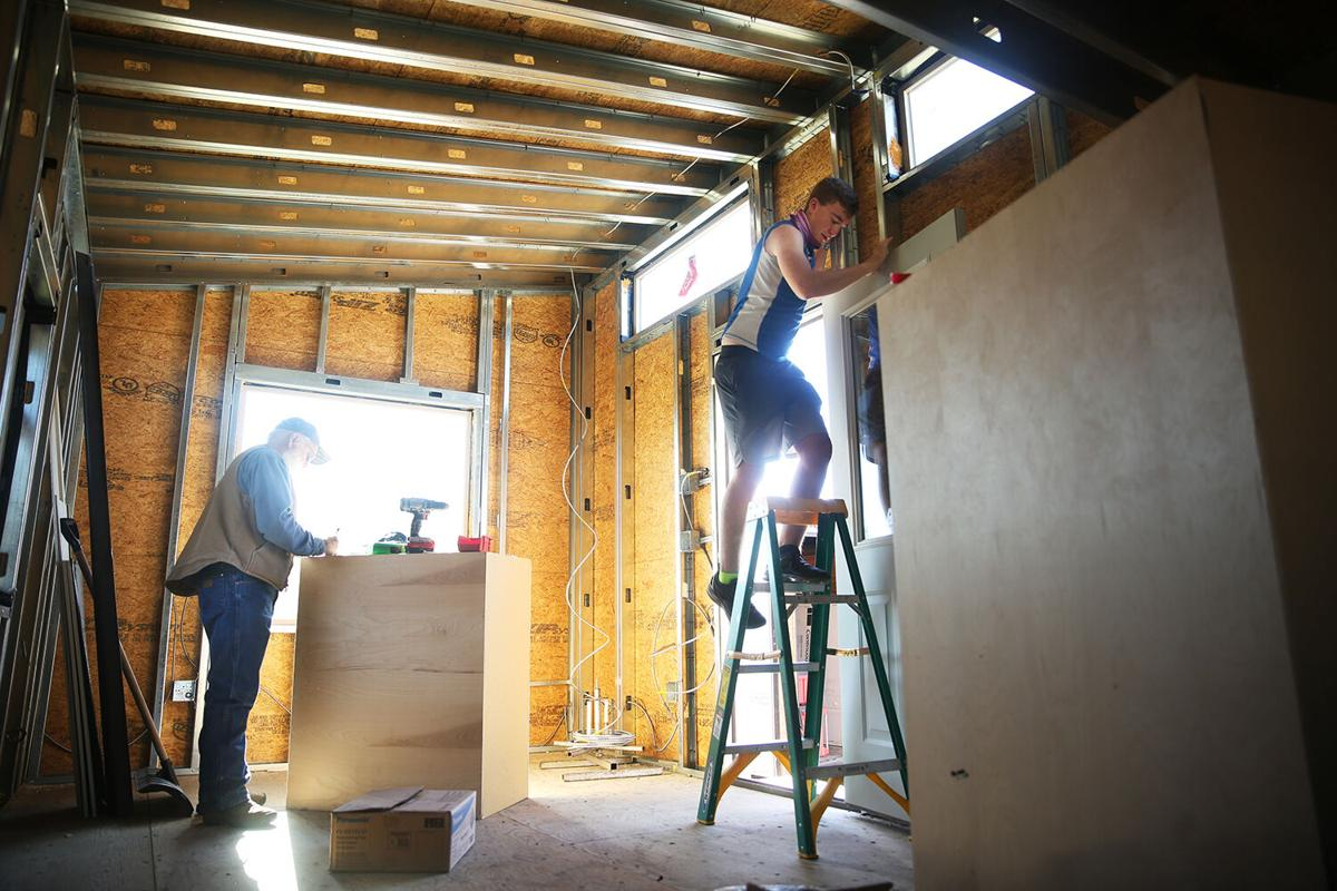 Josiah Bartlett climbs down off the ladder as local electrician Cam Chesbro works on plans