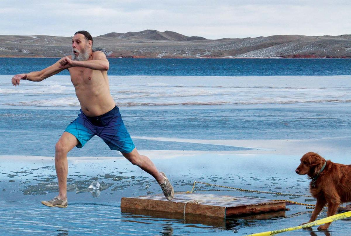 Gary Senier leaps into a frozen Lake Desmet on New Years Day