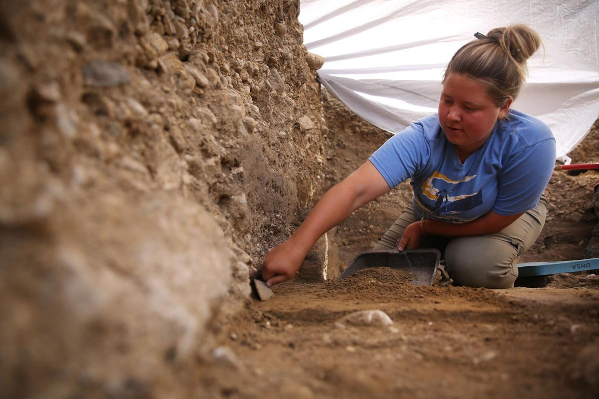 Jolie Magelky uses the trowel to remove a layer of dirt
