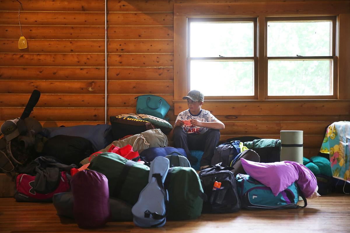 Henry Shoup snacks on a piece of ham amongst the growing pile of sleeping bags