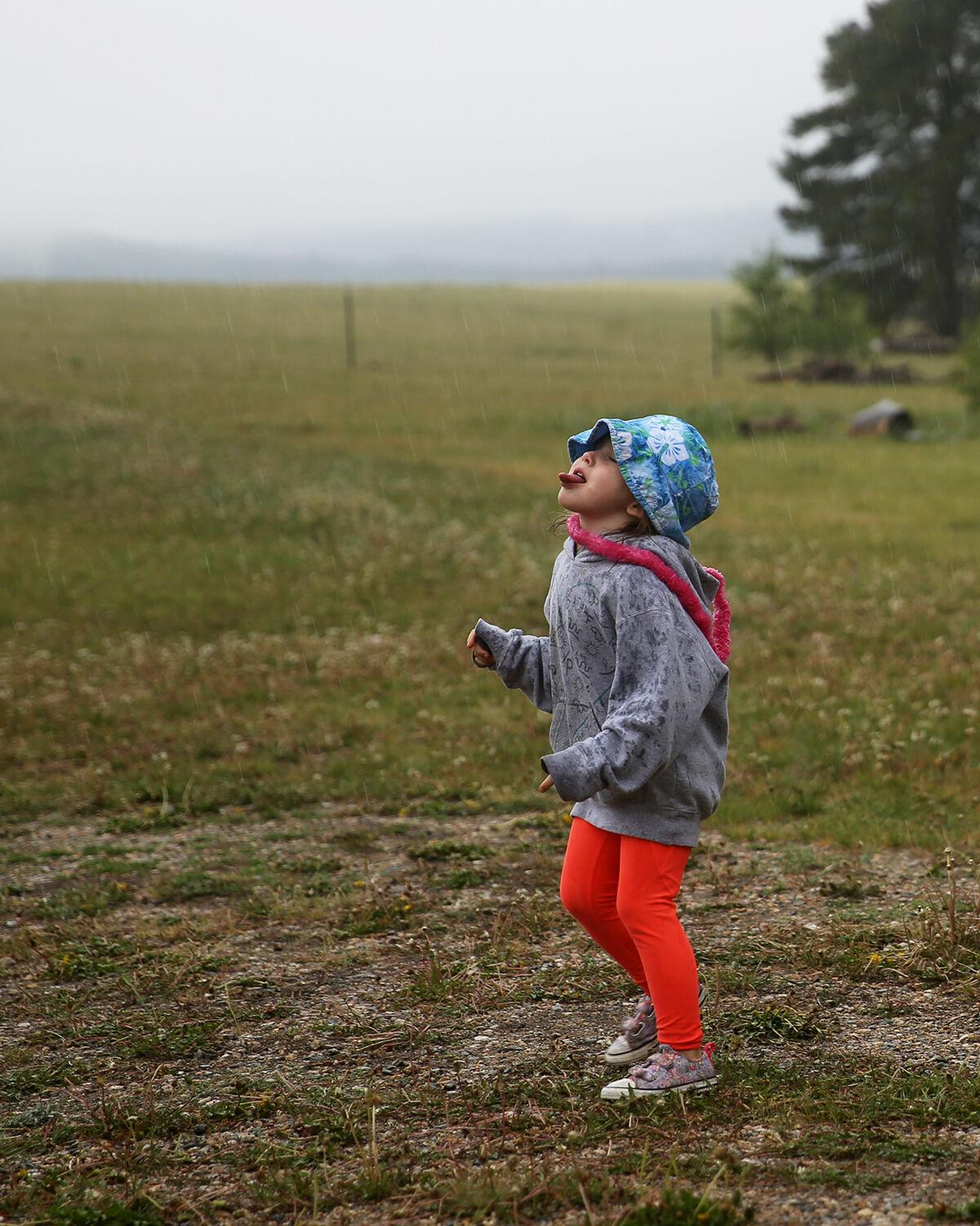 Gracy Alger spins in the rain, catching water droplets on her tongue