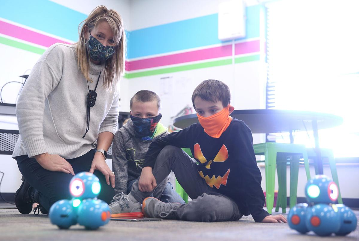 Krista Sweckard works with Griffin Ruby, center, and Sawyer Kolb on their robot pattern