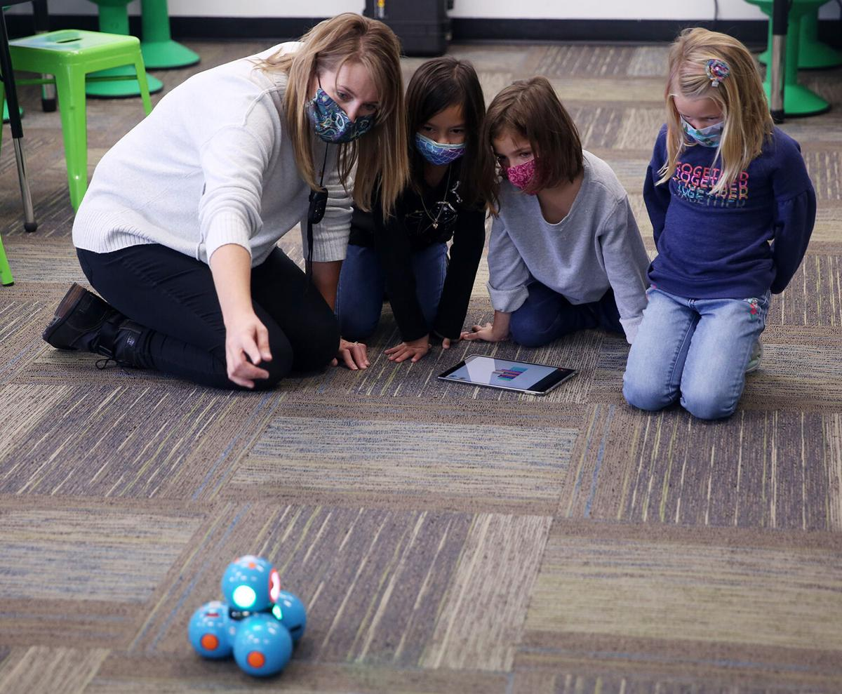 Krista Sweckard points to the robot as she watches the code put together by second graders