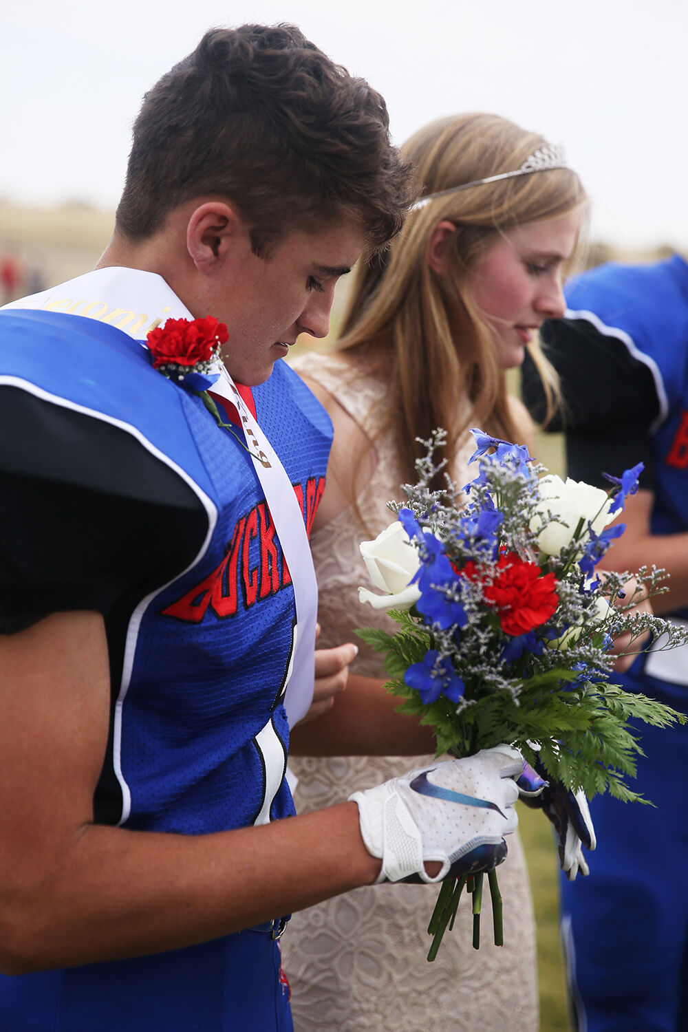 Dylan Fauber hold the flowers for queen Tinley Pierson