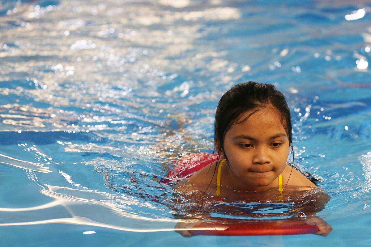 Bianca Soliven, 10, uses her kick board to kick her way across the pool