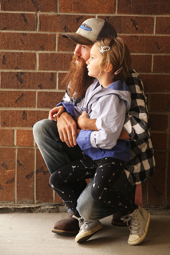 Athena Tarver, 5, sits on the knee of her dad Kelly