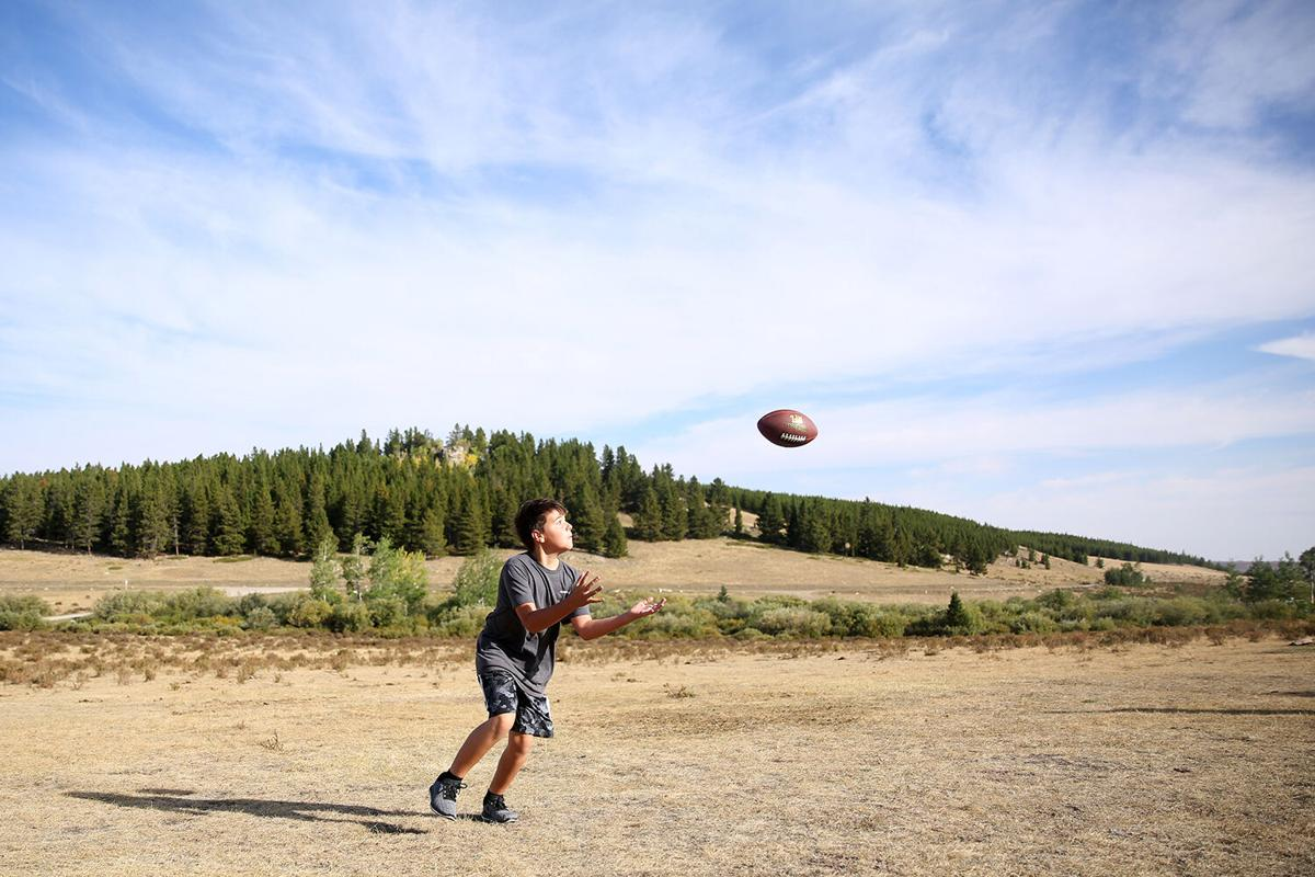 Brody Pullman, 12, turns to catch a pass from great uncle Scott Hedlund