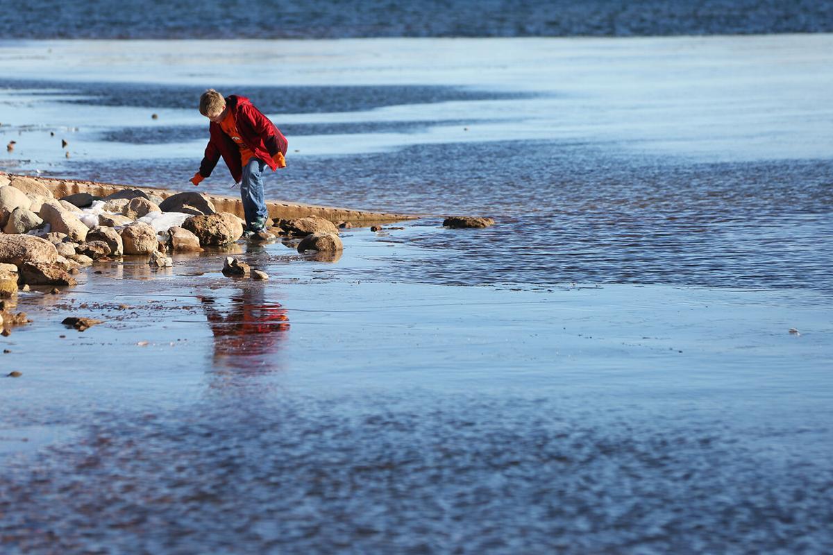 Joey Russell, 8, balances on the rocks near the boat dock