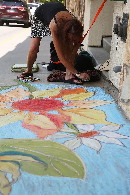Vangie Hansen finishes the edges of her flowery sidewalk square