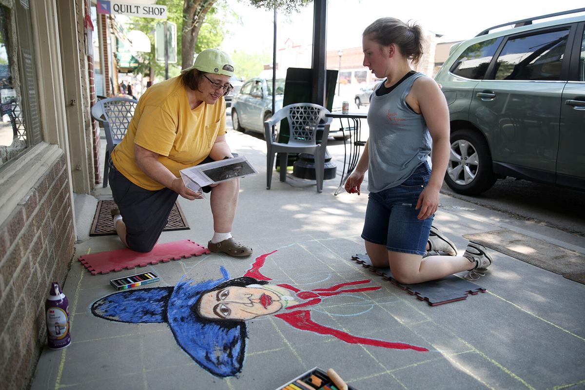 Vanessa Vogel, left, looks at the image that inspired the chalk art