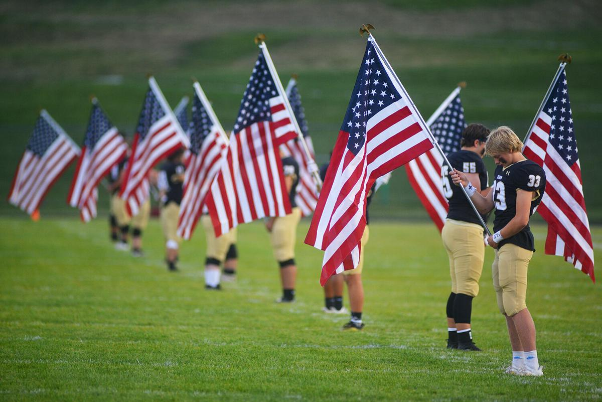 Bryce Camino joins 12 other teammates in holding American Flags