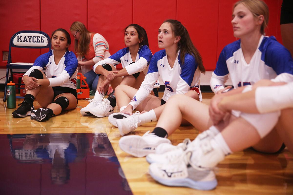 Kaycee's varsity volleyball team sits on the edge of the court