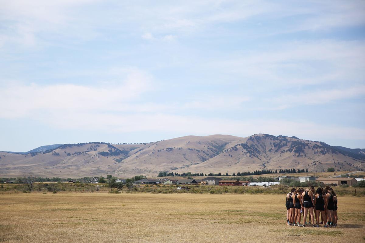 Buffalo's girls cross country runners meet near the starting line for a prayer