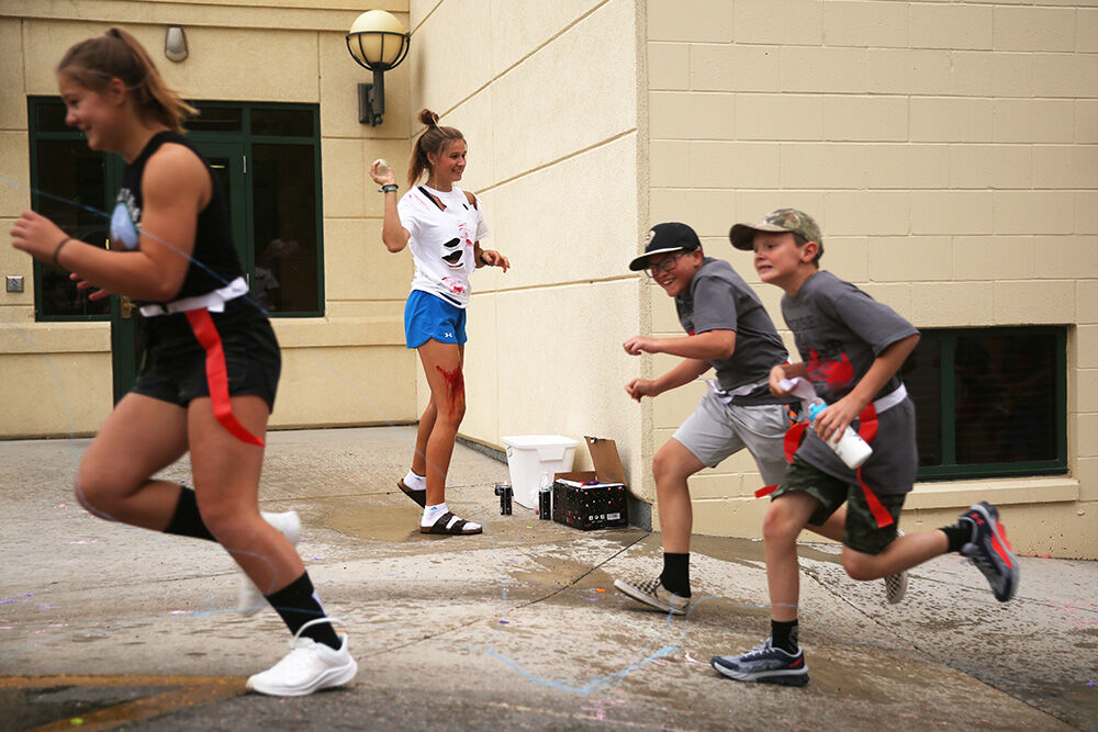 Lexi Rule throws a water balloon at passing runners at the first zombie station