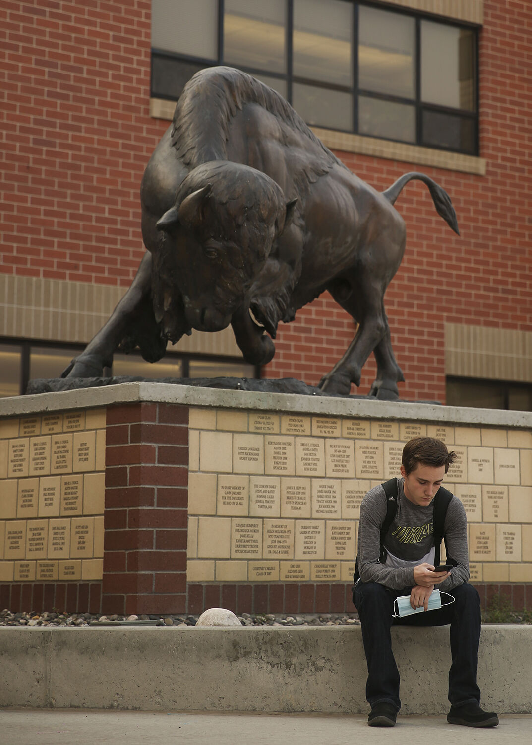 Senior Aaron Dyess sits next to the buffalo statue outside the high school