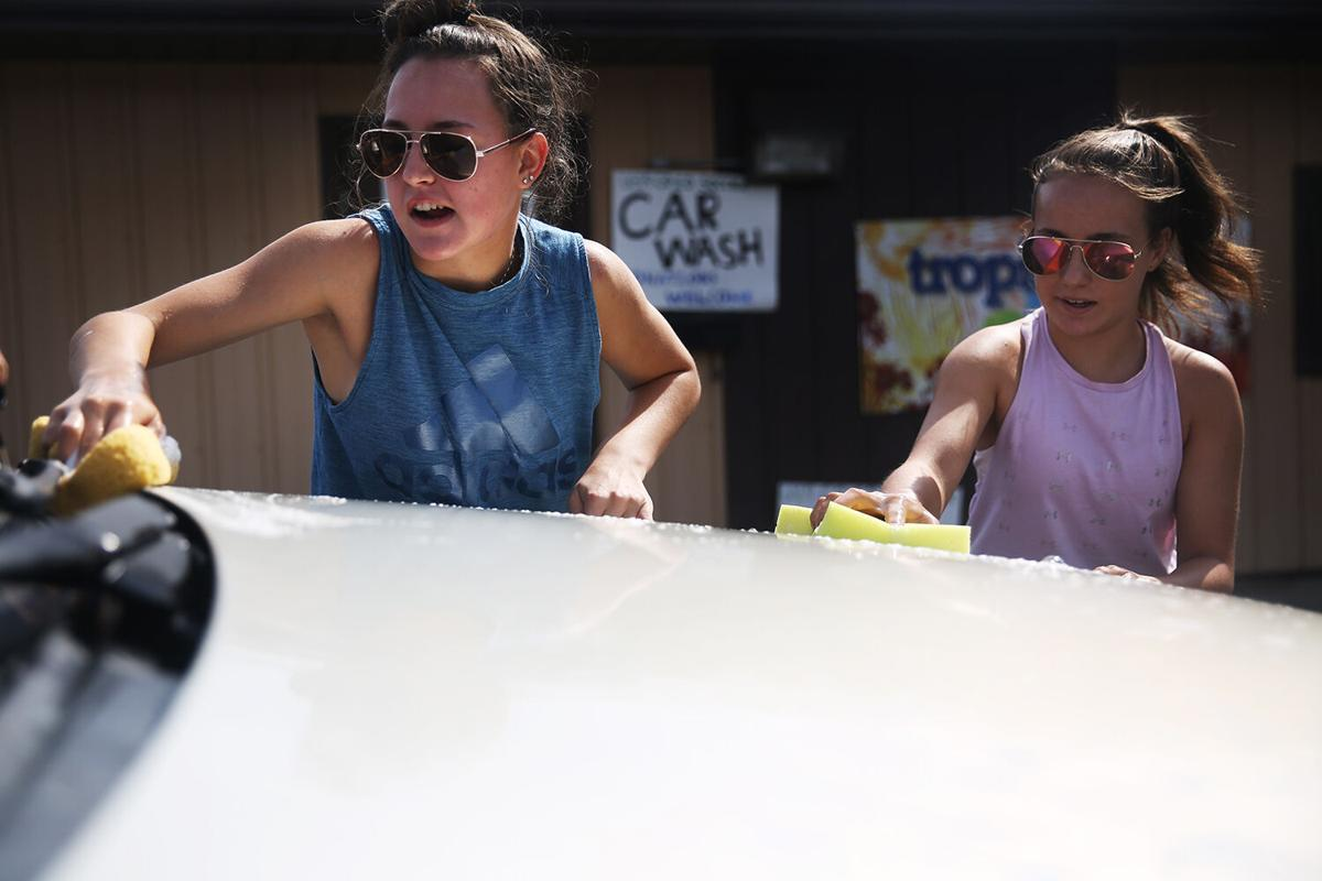 Sisters Olivia, left, and Hannah Zinc scrub the front of a car with sponges
