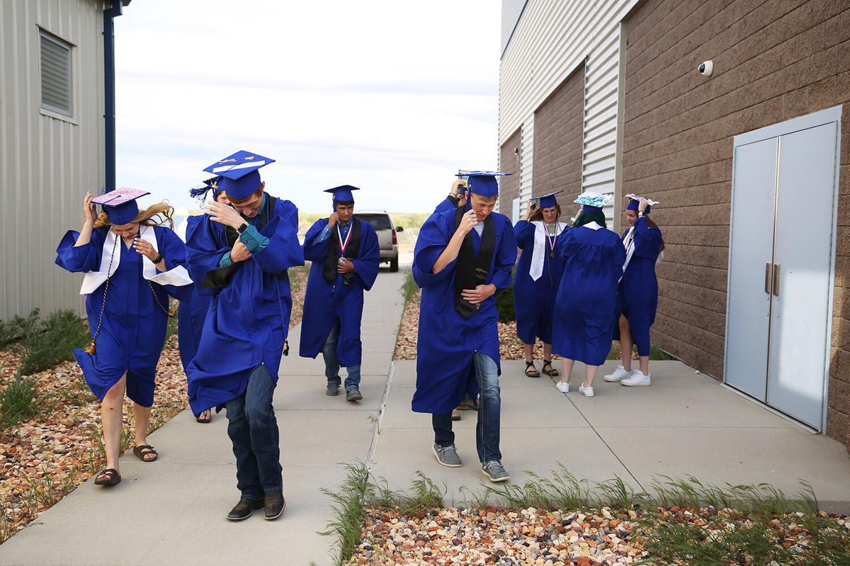 graduates walk back into the school to get out of the wind