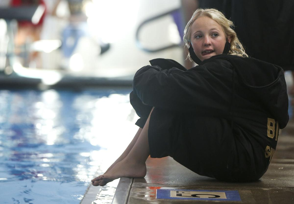 Hannah Southerland sits on the edge of the pool watching the early races