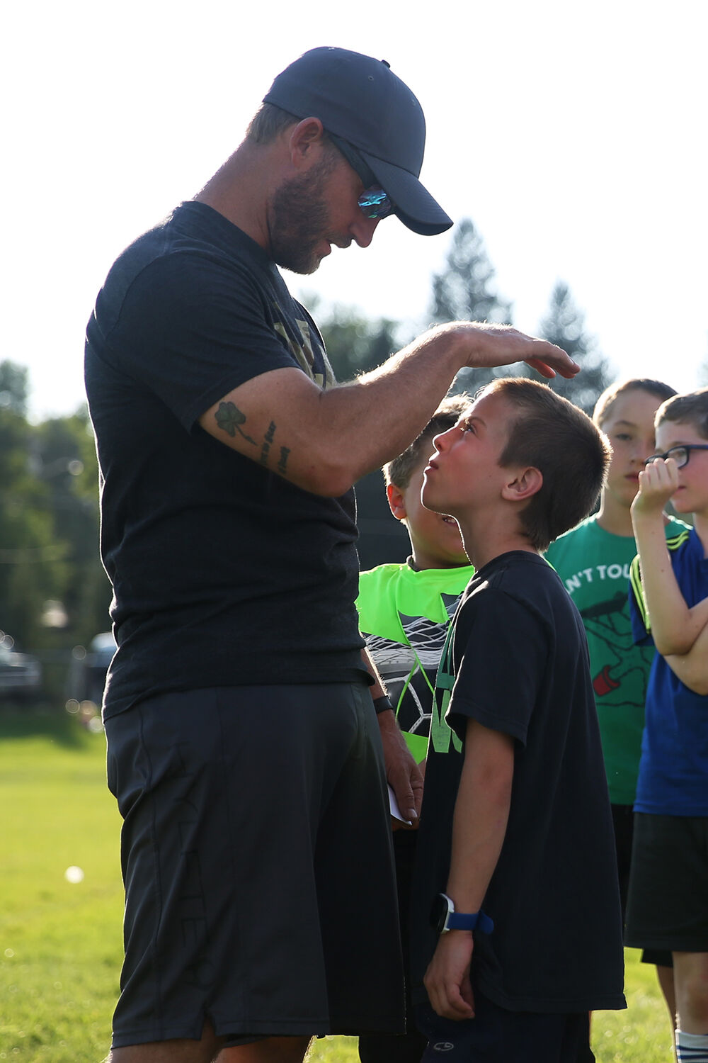 Head coach Parker Ruby pats the head of Tyrus Connors