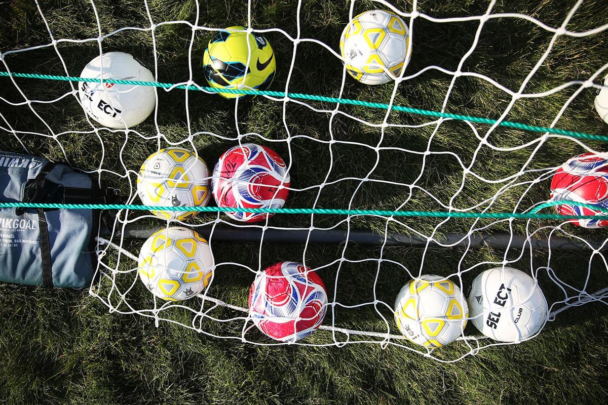 Soccer balls rest in peace under the net as kids do running drills