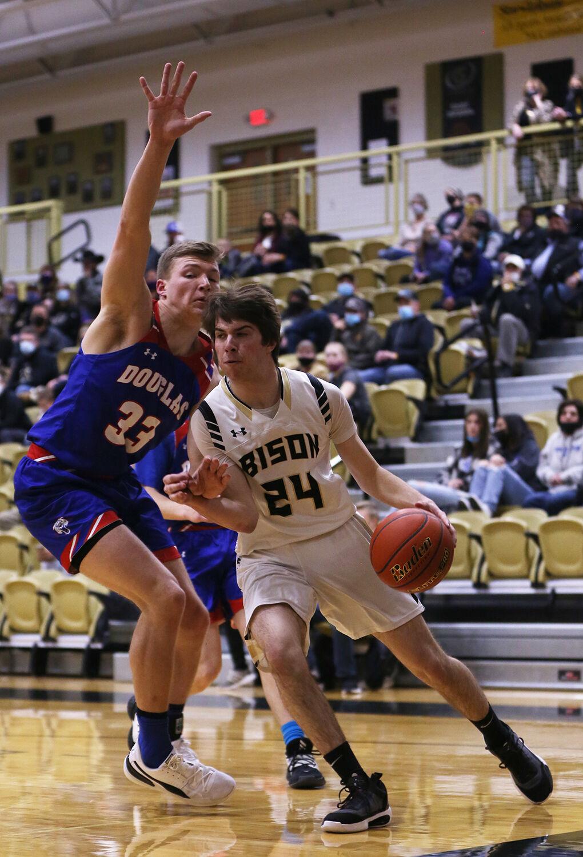 Colby Bessler dribbles under the basket through Douglas defender Garet Porter