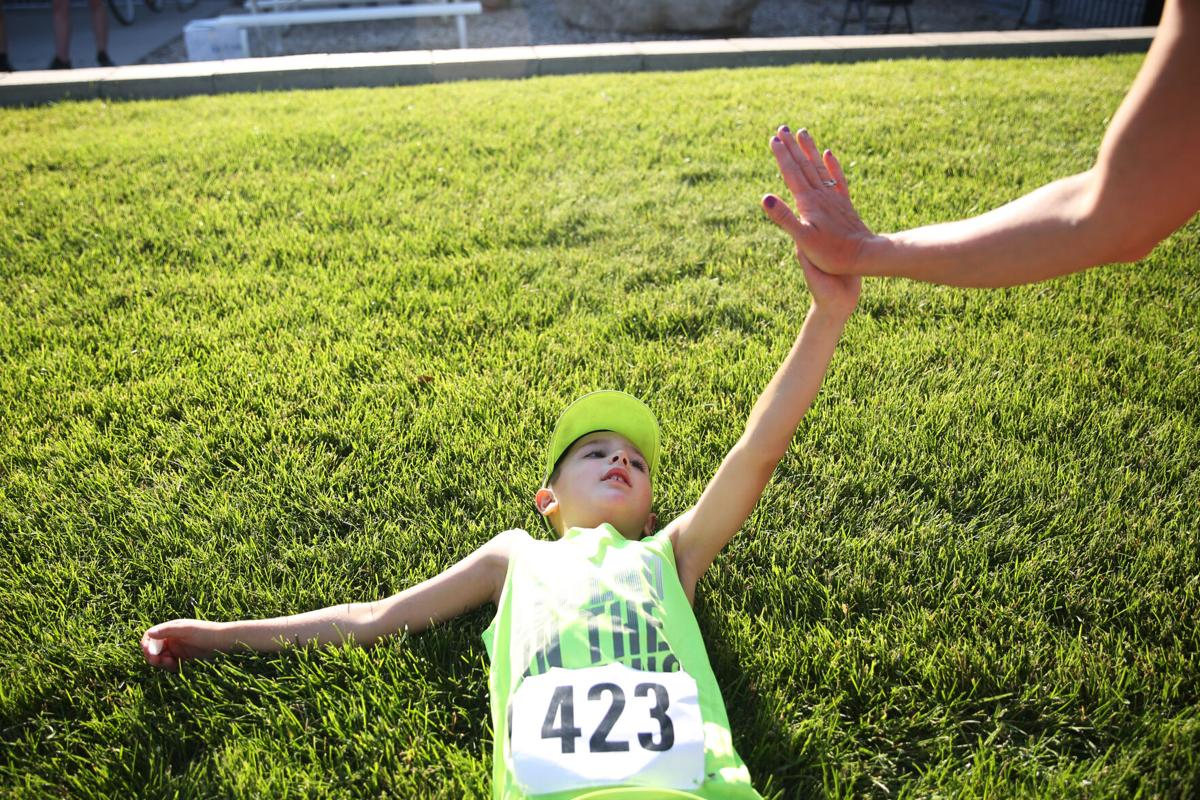 Trajen Mader, 8, sprawls on the ground after completing the 5K run