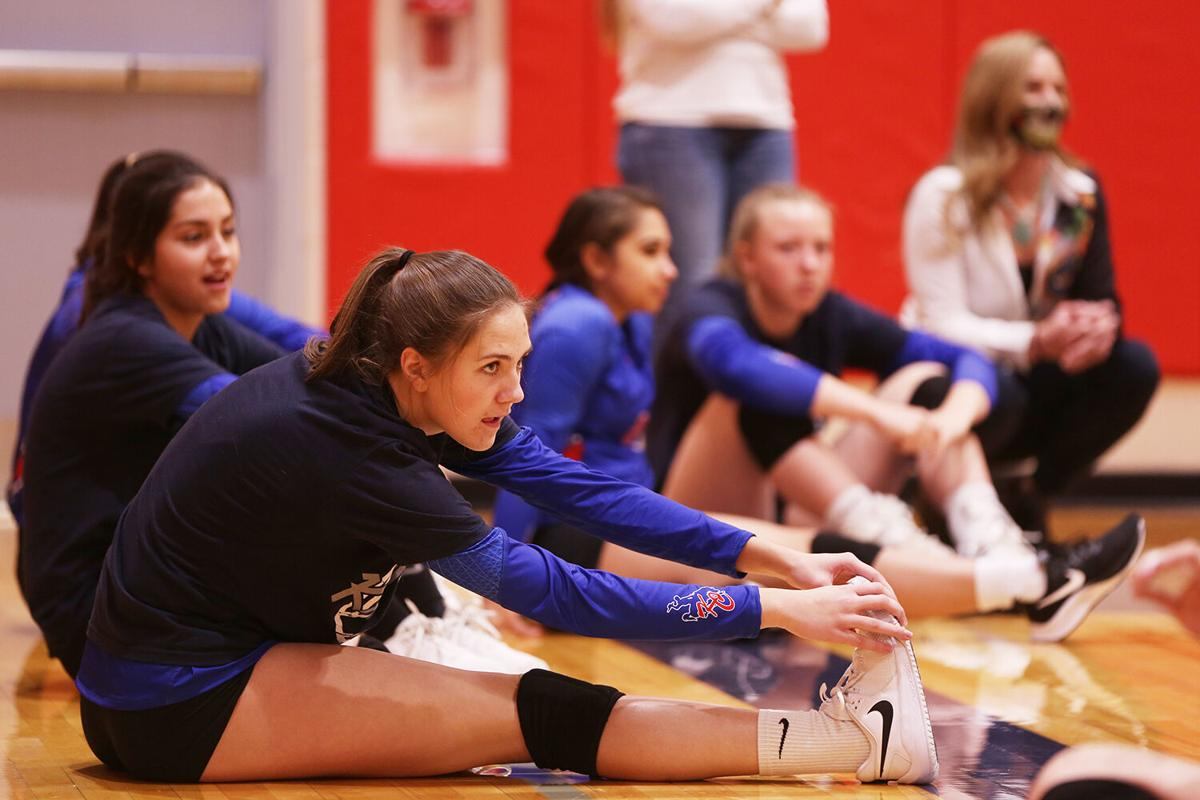 Bindi Hill stretches on the sidelines as the Lady Bucs watch Upton warm up