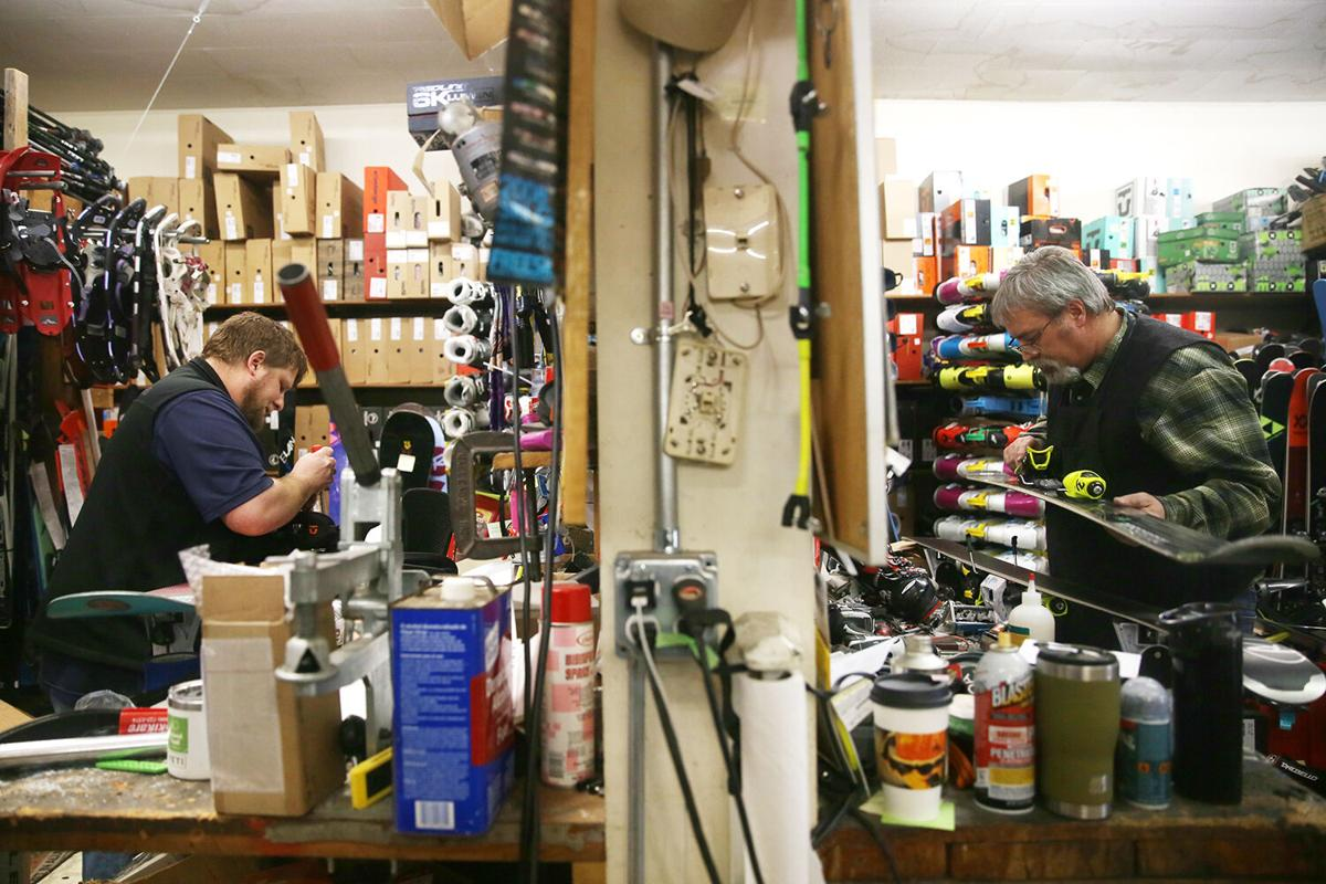 Luke Todd works on one pair of skis, right,