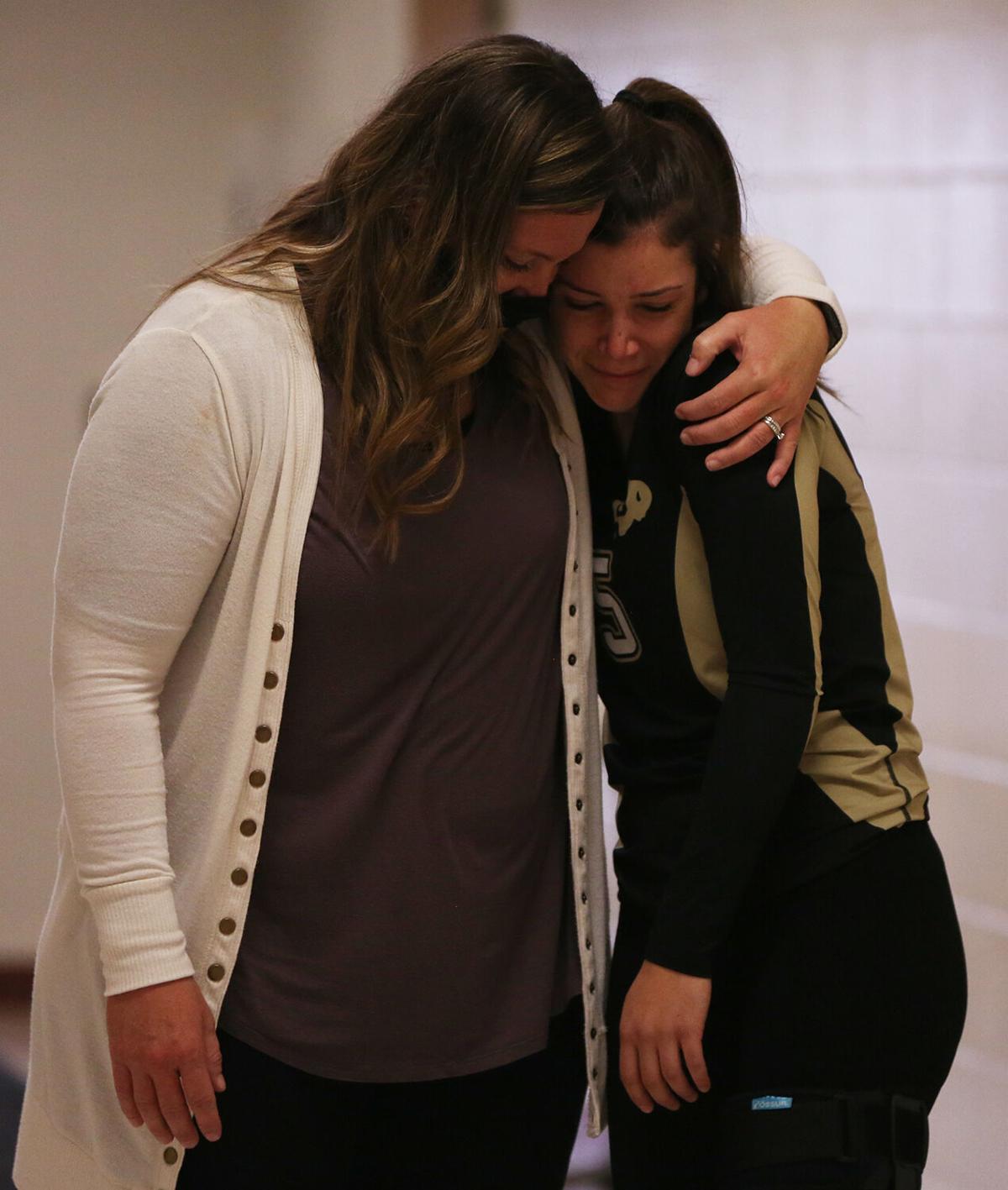 Riley Fowler hugs assistant coach Sarah Walker in the hallway