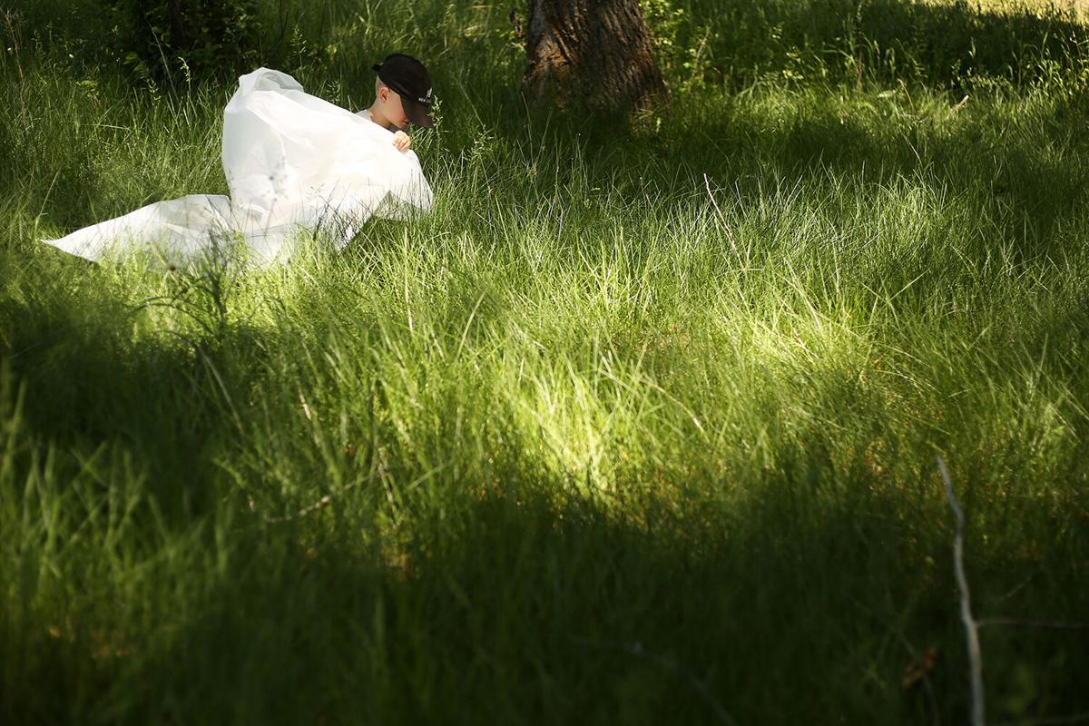 Cohen Dunlap, 6, looks through the grass in search of weeds