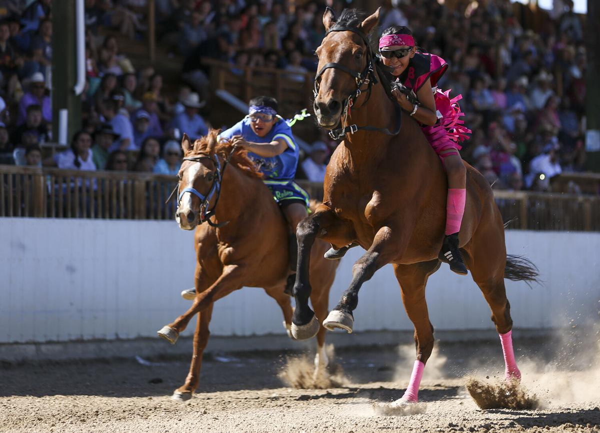 Jayden Ironeyes leans forward with his horse