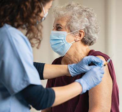 General,Practitioner,Vaccinating,Old,Patient,In,Clinic,With,Copy,Space.