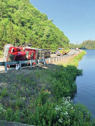 Truck Topples, Dumps Logs Into Lake