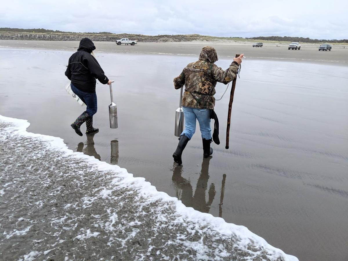 Women dodge waves while digging for razor clams