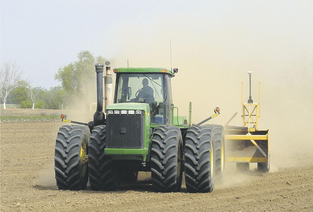 Rice growers ready fields in rain