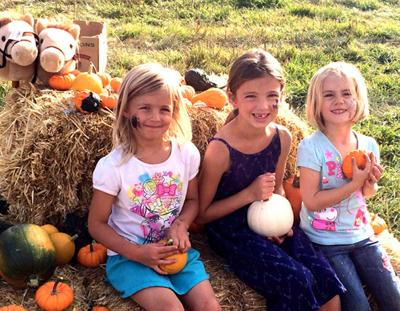 Happy girls hold pumpkins